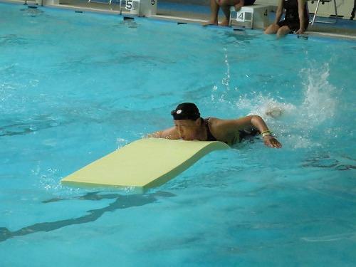 ロングビート板を使ったパドリングリレーで力泳する参加者。皆、慣れない体の動きに一生懸命挑んでいました