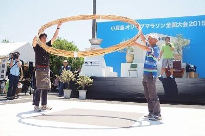 タガの重さは13kg。左が大会を発案した山本康夫さんです。 昨年の優勝者は、この大きな輪を225回も回しました。はたして今年は・・・