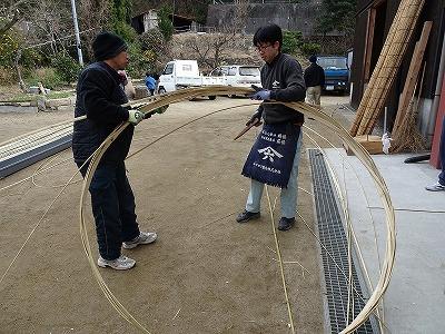 タガを編む山本さん(右)と大工の坂口町会議員。 山本さんは、この大きな輪をフラフープにすることを思いつきました