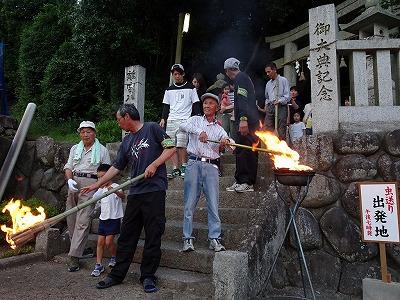 神社の入り口で、子供たちの火手に火をつけています。火手は、一度火をつけたら20~30分は燃え続けるように松脂や布を使って工夫しています