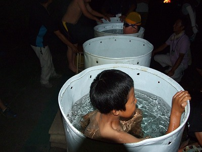 ドラム缶風呂に入る男の子。よく見ると缶の内側も白い塗料でコーティングされています