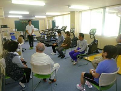 新しくなったトレーニングルームで真剣に指導員の話を聞く参加者の皆さん