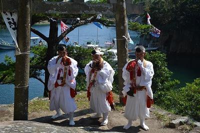 「奇祭」の神事を執り行う大島神社の神主の方々。風待ちの入り江が背後に控えています