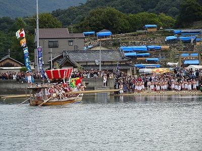 最終目的地の宮の浜をめざして力漕する「皇子丸」。陸地では、到着を待って大勢の人が詰めかけています