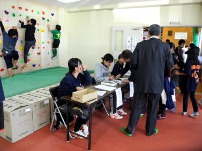 体育館ロビーで地元の中学生が受付のお手伝い。その後ろでは子供たちがボルダリングで遊んでいます