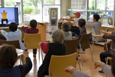 ロビーに設置したテレビで映像を観ながら運動をする参加者
