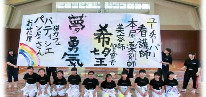 将来の夢を大きな和紙のキャンバスに大書した児童10人
