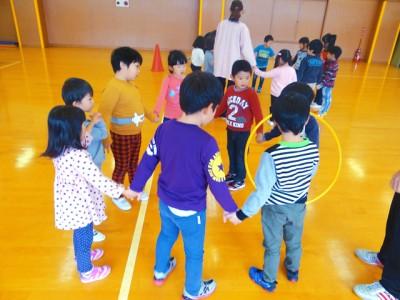 運動あそび「フープくぐり」(5歳児)、みんなで輪になって、フープをくぐります。