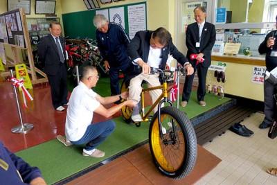 納品された自転車(ファットバイク)にまたがる村上英人蔵王町長