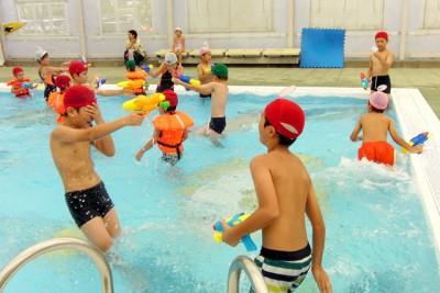 幼児プールで水鉄砲合戦を楽しむ