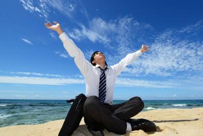 開放的な海岸の砂浜に胡坐をかいて、大きく伸びをするサラリーマンの画像