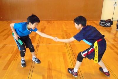 ニュースポーツの一つ、タグラグビーの教室で、タグを取り合う練習をする男子児童2人