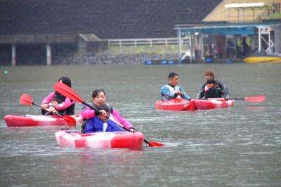 大学生と子供もカッパ着用でカヌーを漕ぐ
