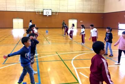 向かい合って、ボールを落とさずパスする練習をする子供たち