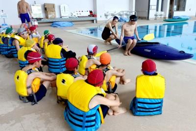 カヌーの乗り方、降り方を学ぶ子供たち。2人で協力して正しい乗り方、降り方を説明