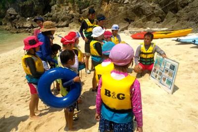 小さい子供達の参加が多かったので、ライフジャケット着用と効果、海の危険生物の説明を行いました。サンゴ礁にも見かける、オニヒトデ、ガンカゼ、ミノカサゴ、浜辺にも打ちあがるカツオノエボシなど、生物特徴や生息場所を説明している様子です
