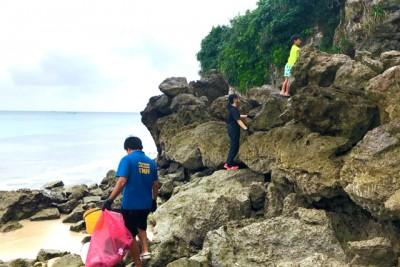 岩場のごみを取るするために上っている子供たち