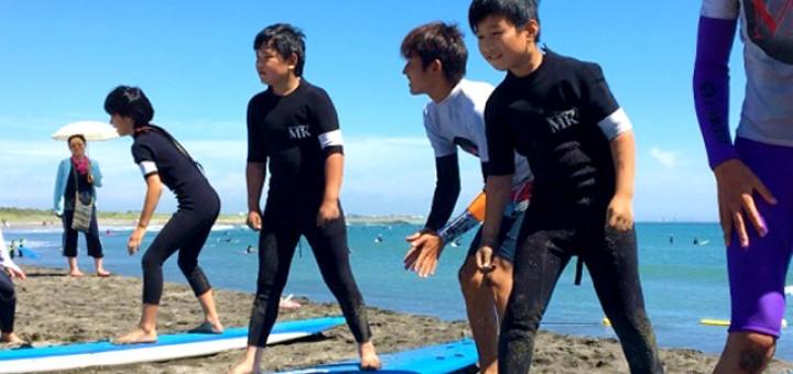 まずは陸上でのサーフィンに乗る練習から。教えてもらいながらサーフボードに乗ってみる子供たち