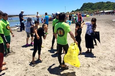 ビーチクリーンで心もクリーン。ゴミ袋を手に、ビーチの掃除をする参加者とスタッフの様子