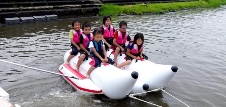 写真は昨年7月1日。 フェルティバルのトリを飾ったバナナボート体験。ライフジャケット浮遊体験や、雨の中で全身ビショ濡れ状態なので、バナナボートで濡れても全然平気。「落として!落として」という子も
