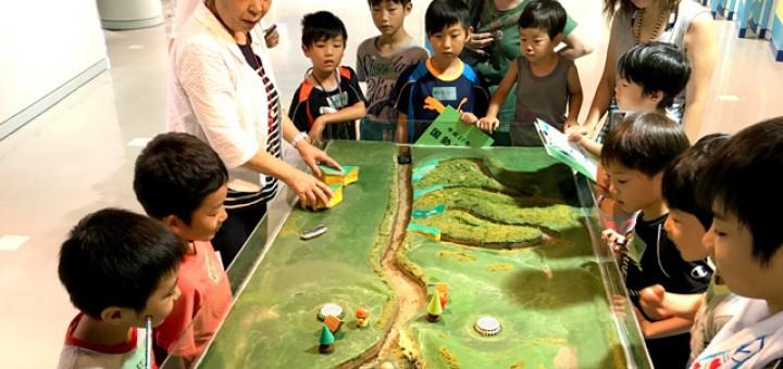 子供たちが開設の担当者から模型を見ながら学んでいる画像