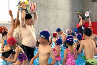 大人のスタッフが頭に掲げるカゴにボールを入れようと一生懸命な子供たち