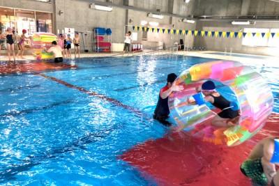 ウォーターキャタピラレースの様子。円筒型の浮き輪のようなウォーターホイールに乗って、ハムスターのように中で回りながら、水面を進みます。