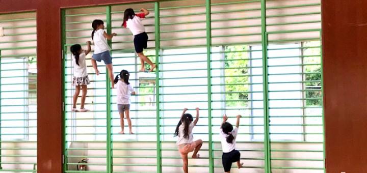 窓の前についている金属の柵をよじ登る女の子たち