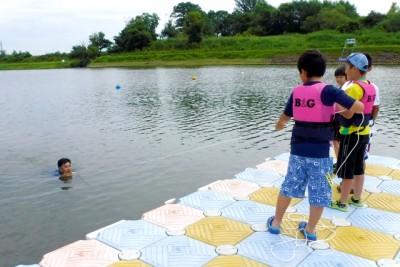 水辺の安全教室で参加者が指導員をペットボトルで救助。初めはペットボトルが届かず何回もやり直した。最後は見事救助に成功