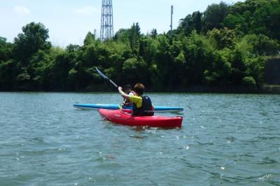 川の上をカヌーに乗って漕いでいる様子