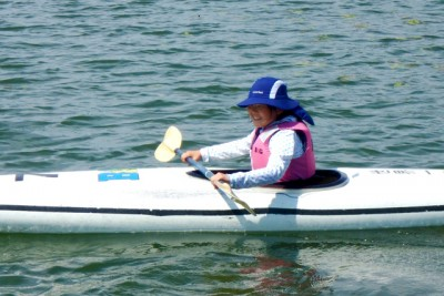 楽しそうに一人でカヌーに乗っている笑顔の女性