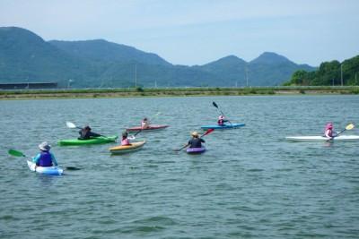 1人用のカヌーに乗った6人の人々が川面に浮かぶ