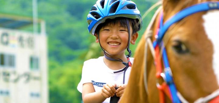 乗馬を楽しむ少年。極上の笑顔がまぶしい。