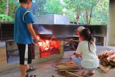 薪をかまどにくべている子どもたち。どのくらいの火加減がいいのかなあ…