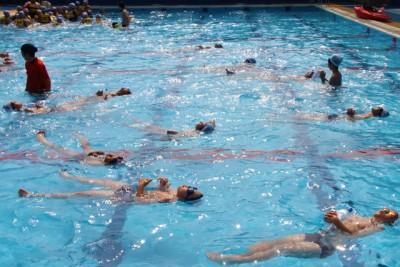 水辺の安全教室で、空のペットボトル一つを使って背浮きをして、助けを待つ「ペットボトル浮き」の練習風景