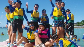 ライフジャケットを着て海遊びをする子供たちの画像