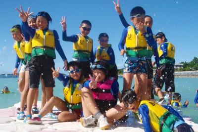 ライフジャケットを着て海遊びを楽しむ子供たちの画像