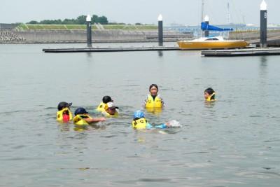 ライフジャケットを着て、海の中で泳いで楽しむ子供たち