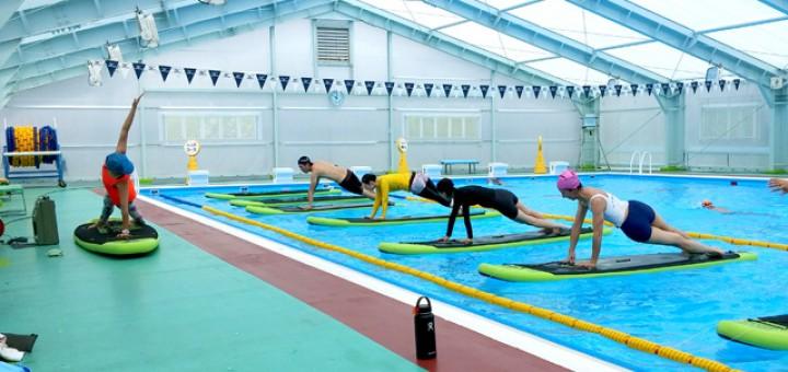 プールの中にSUPを浮かべてその上でヨガのポーズに挑戦している参加者の皆さん