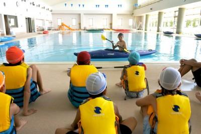 指導員がカヌーの乗り方、下り方、漕ぎ方を説明