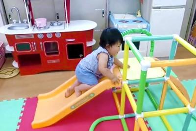 大きな組み立て式の滑り台で楽しそうに遊ぶ赤ちゃん