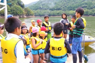 ライフジャケットを着て、岸辺で説明を受ける子供たち