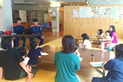 海洋センターの室内で、消防士のお話を聞く親子