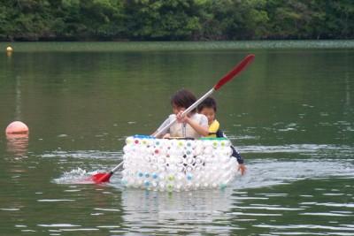 完成したカヌーに乗っている兄弟