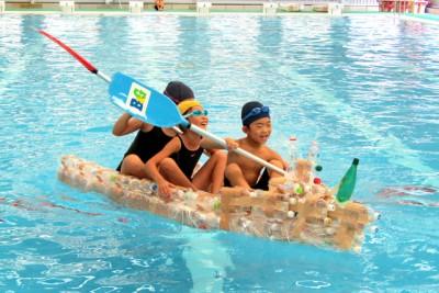 出来上がったペットボトルカヌーを、プールで楽しむ3人の子どもたち