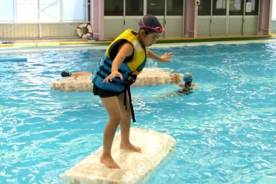プールに浮かべたペットボトルで作ったいかだに乗ってバランスを取っている子ども