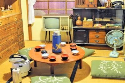 昭和70年代の家庭の写真。和室、丸いちゃぶ台に座布団、ブラウン管テレビ。