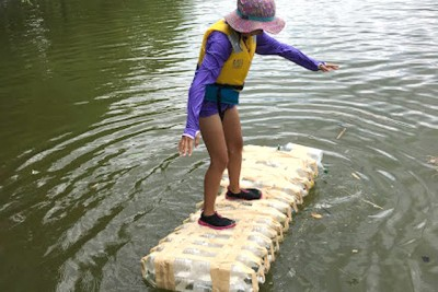 川の上に浮かべたペットボトルいかだに乗って、バランスを取っている子ども