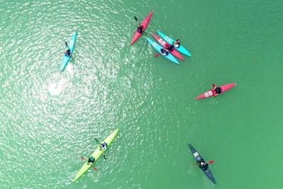 川の上から真下に浮かんでいる色とりどりのカヌーを空撮