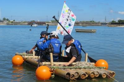 竹のイカダに乗って海に漕ぎ出す3人の男の子たち